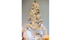 Menggambar Rangka Pohon Natal di Dinding Yang Dihiasi Lampu Serta Ornamen Unik
